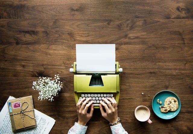 person typing on yellow typewriter
