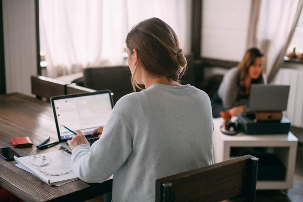 woman typing on computer working from home as a virtual assistant